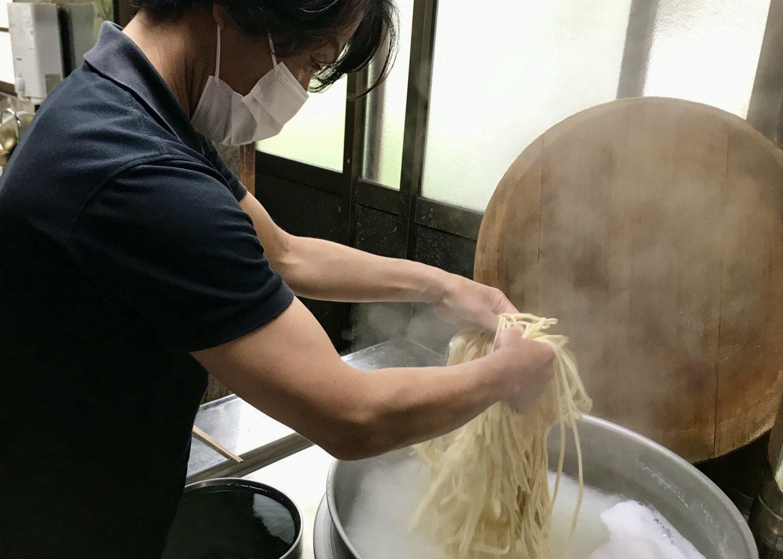 慣れた手付きでうどんをバラしながら湯釜へと投入する細川さん。