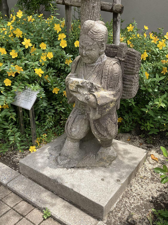 町屋六丁目児童遊園の金次郎。やはり植え込みにひっそりと設置されている(2021年)。