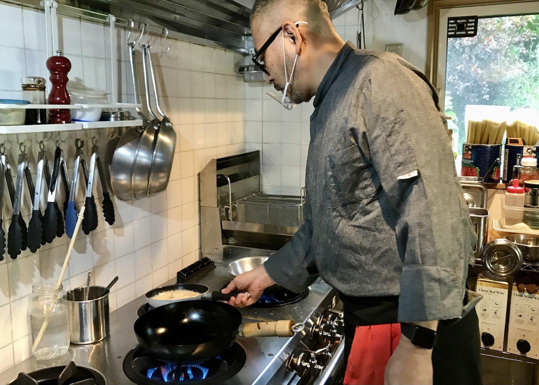 エビとトマトのクリームソースを火にかける高田さん。その堂々たる身のこなしは、どこからどう見ても生粋のシェフに見えるのだが……。