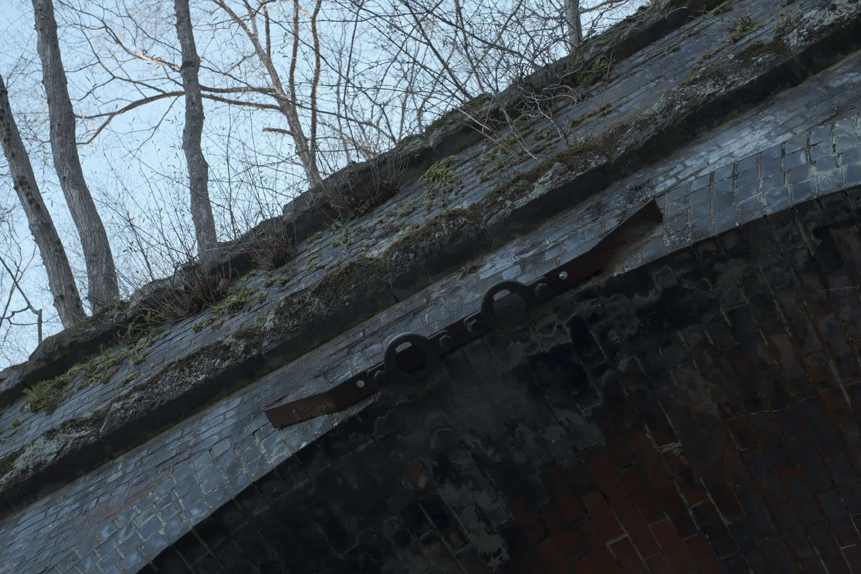 第7トンネル横川方はピラスターも立派なレンガ造り。ポータルのアーチ上部にある金具は電信線やケーブルを吊すものだった。現役時の映像や写真にも写っている。