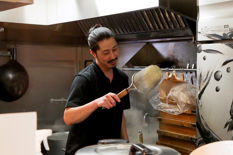 縛り髪に完璧な黄金比の生え際を持つ、店長の菅野稔さん。