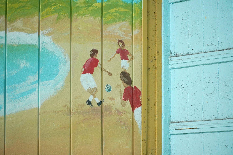 ペンキ絵の端に、サッカーをする子どもたち。もちろんユニフォームはレッズの赤だ。
