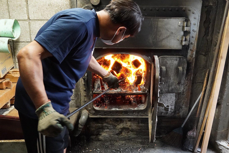 薪を焚き続ける、3代目店主の坂下三浩さん。