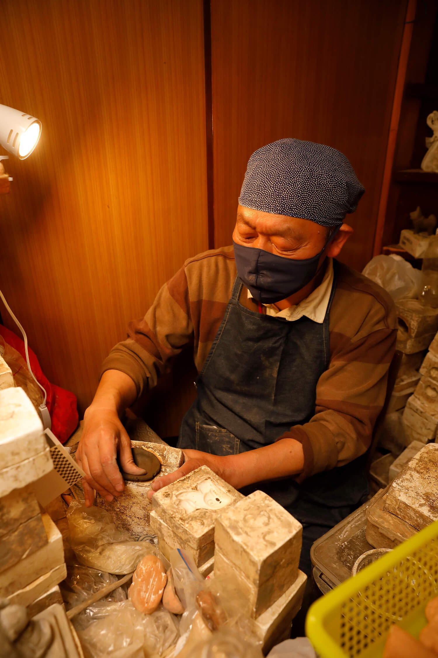 割型にのした粘土を詰める吉田さん。