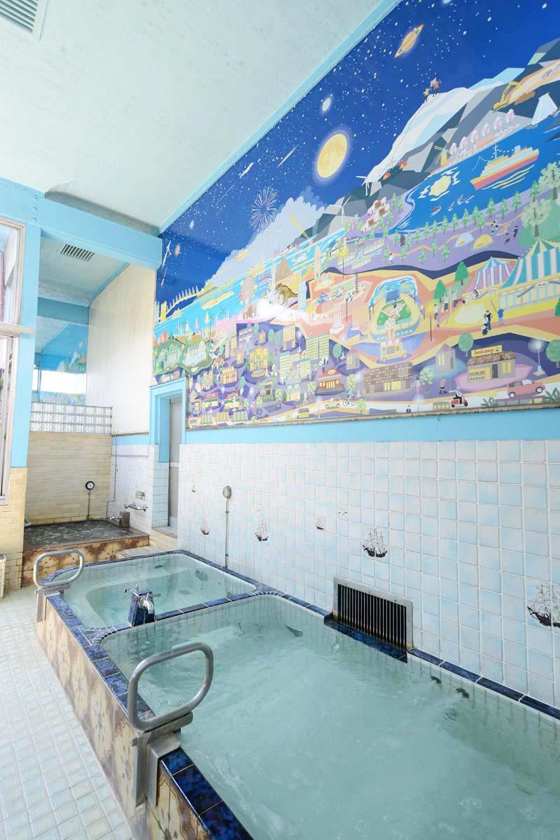 大きな浴槽を2つに仕切り、大小の浴槽で湯温を変えている。奥は日替わりの薬湯。