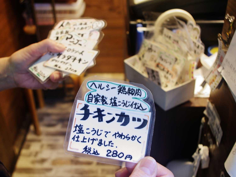 両手に持ちきれないほどある商品のプライスカード。