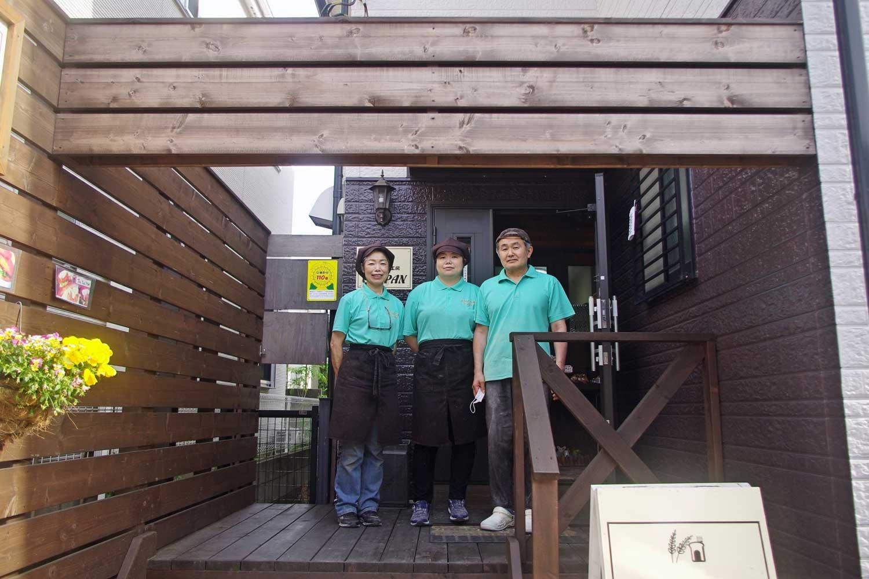 山小屋風に改装した入り口のウッドデッキに立つ比嘉さん一家。