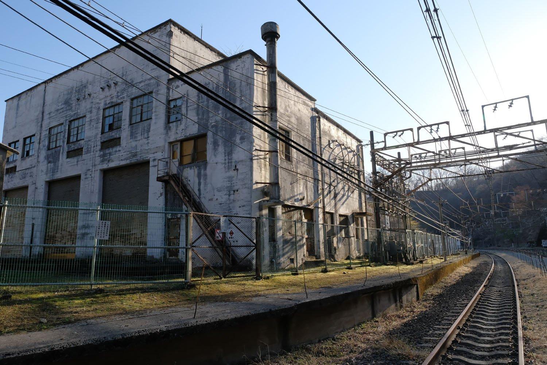 昭和12(1937)年築の変電所建屋は現役時の姿を色濃く残している。夕刻の斜光で新線下り線のレールが光る。