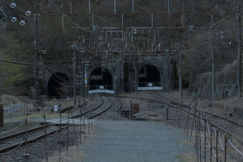 軽井沢方は3つのトンネルが口を開ける。右から、新線上り(アプト式上り用引上線を転用)、新線下り(アプト式本線を転用)、旧国道からのアクセス用自動車トンネル(アプト式下り突込線を転用)。レベル(平坦な)状態の突込線と上り勾配の下り線のトンネル段差に注目。熊ノ平の先も一気に登り坂となっていた。