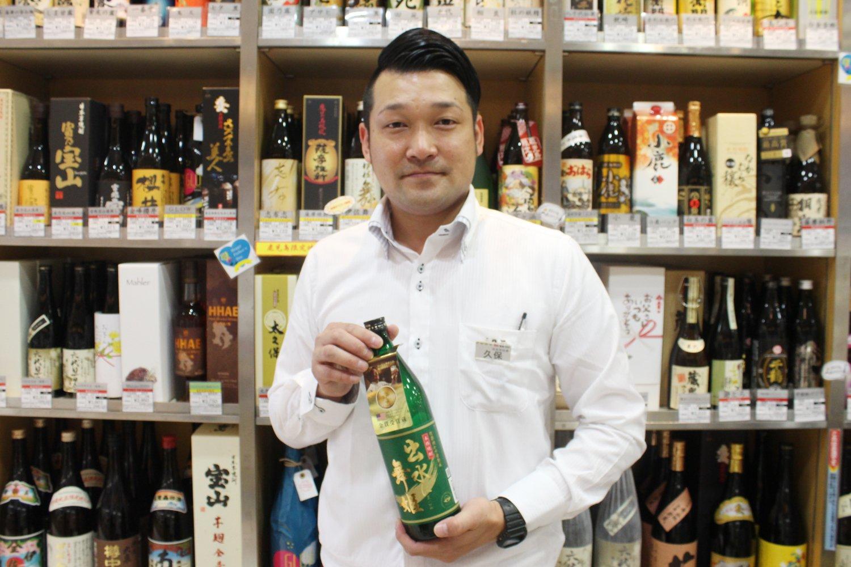 酒瓶がずらりと並ぶ、焼酎コーナーで待ち受ける副店長の久保さん。