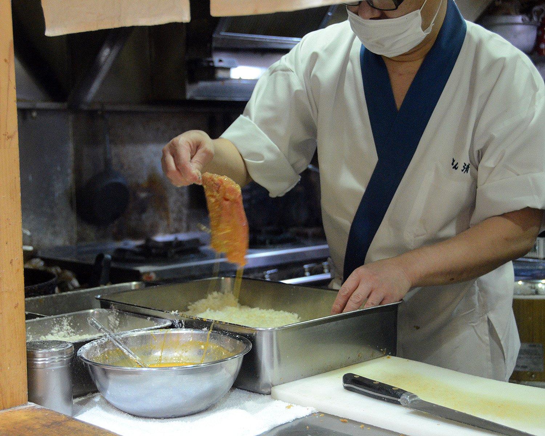 たっぷりの卵に肉をくぐらせた後、パン粉の中へ。このパン粉もあのサクサクの食感の源に。