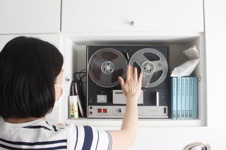 自分の家から持ってきたオープンリールのテープをセットするおかもとさん。