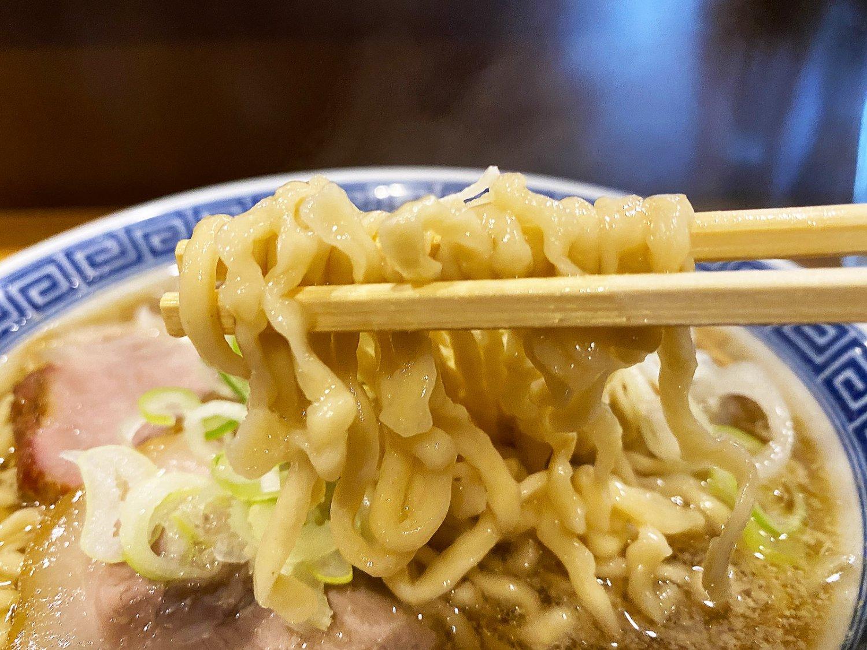 スープが絡みつく中太ちぢれ麺は自家製。もちもち食感がたまらない。
