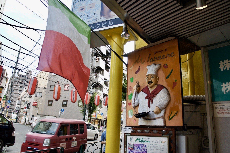 『メランツアーネ』店舗入口。イタリアンシェフの看板に歴史を感じる。
