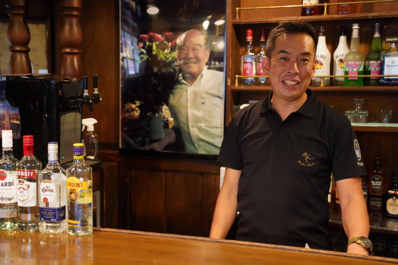 先代の大きな写真が飾られたバーカウンターでほほ笑む、2代目店主。