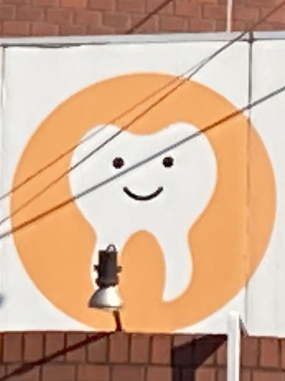 電車から見えるところにある看板。一目で歯医者とわかるキャラ(千歳烏山・2021年)