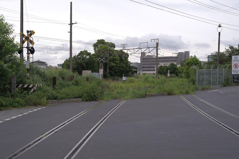 「塩業」と表記された踏切。奥が高島貨物線。複線分の線路がある。