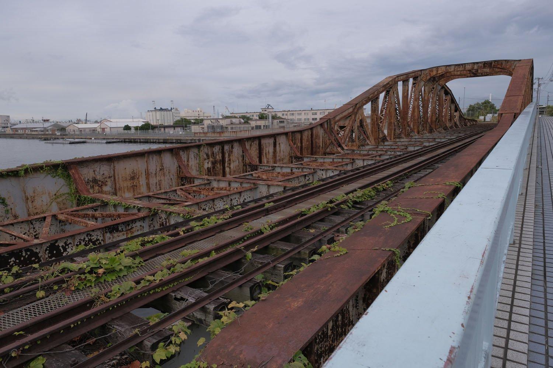 瑞穂橋のプレートガーダー部分。主桁は水平ではなく曲弦トラスへ向かってせり上がっている。レールはまだ敷かれたままである。背後は米軍基地。