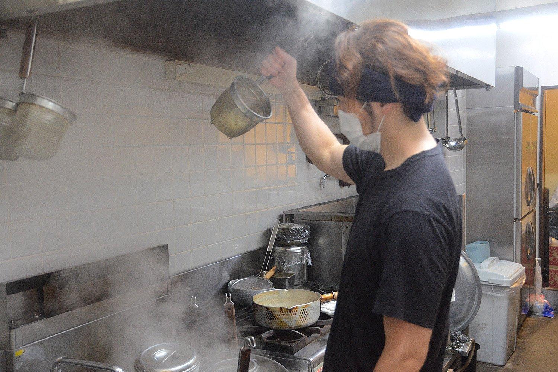 麺の湯切りシーンを撮影。整理された厨房は「仕事ができる人はみんな持ち場をキレイにしていた」という西川さんの修業時代の体験に基づいている。