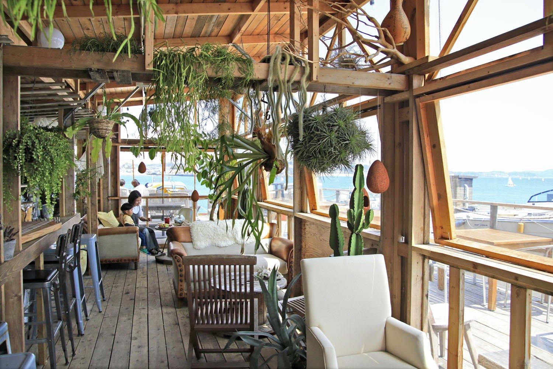 熱帯植物、ソファ、木製電線リールのテーブルを配し、居心地最高!