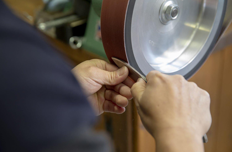 グラインダーで鋼材を削る。
