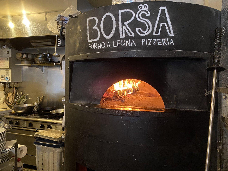 窯もイタリアから輸入。着火しやすいが安定しない細い薪と、着火しにくいが一度着くと安定する太い薪、2種類を使い分けながら窯内の温度を500度ほどに上げていく。
