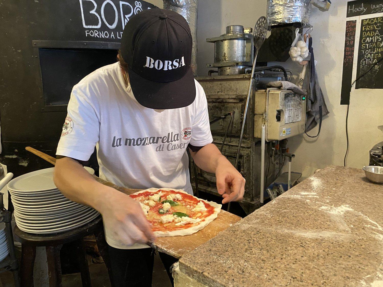ソースやチーズ、トッピングを乗せたピッツァを窯へ入れるのにも熟練の技が求められる。