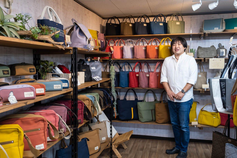 郊外にある縫製工場を兼ねた店舗で帆布製品に囲まれる小曽戸聡さん。