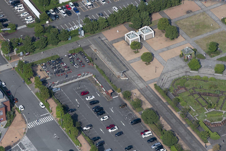 上から見ているので地面と同系色になって擬態化しかけているが駐輪場右横に短いプラットホームとT字状のホーム屋根が見える。保存された横浜港駅の一部分である。線路も分かる。