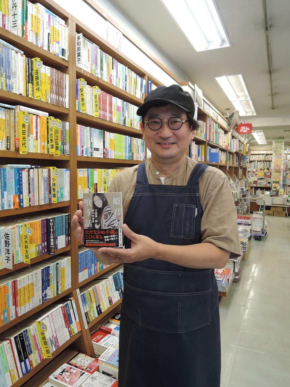 オススメの『姫君を喰う話 宇野鴻一郎傑作短編集』を手にする笈入建志店長。