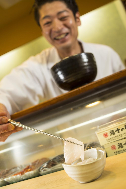 クエのしゃぶしゃぶをポン酢の器に盛る森田さん。