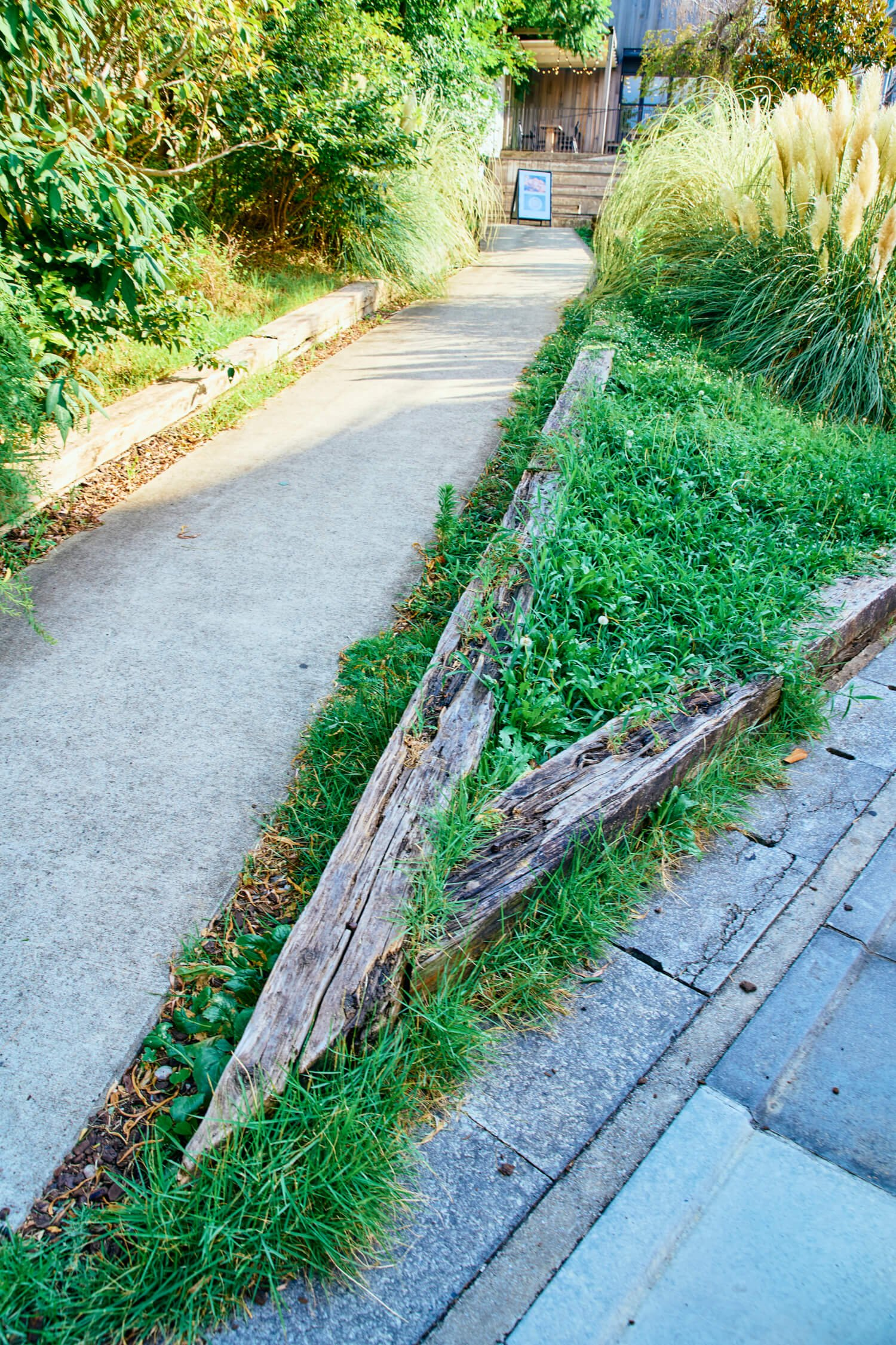 東横線で使用された枕木を土留めや看板に活用。ナチュラルガーデンのよう。
