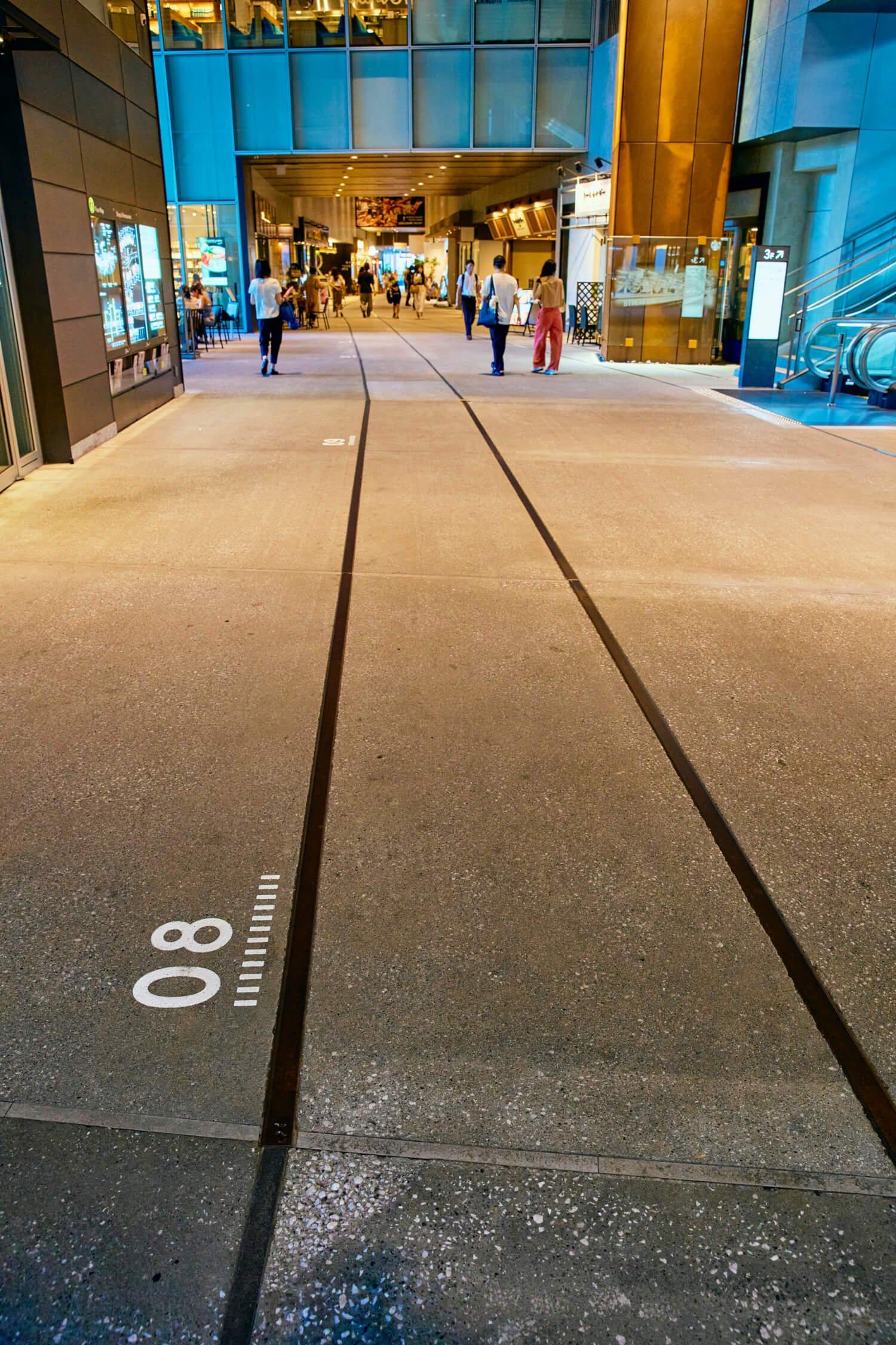 一部本物のレールを敷く2階貫通通路。かつての高架橋の柱番号も。