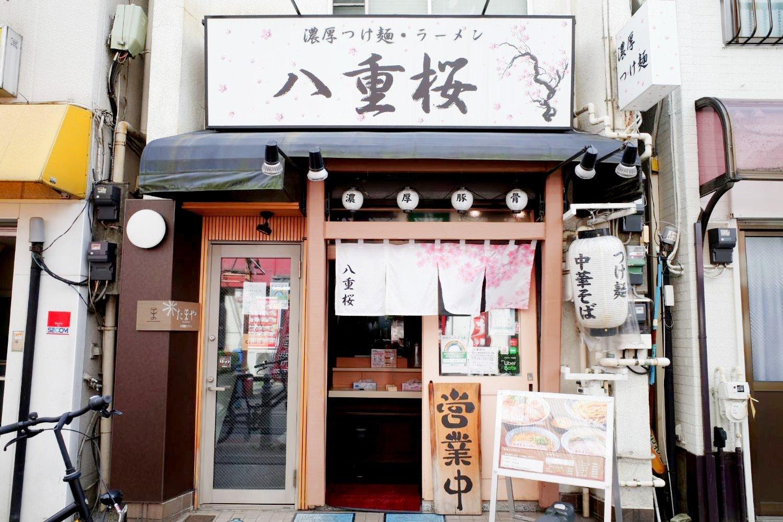 王子のシンボル的レトロマンションである飛鳥山スカイハイツを囲むように小さな店が並ぶなか、目に入る八重桜の看板。