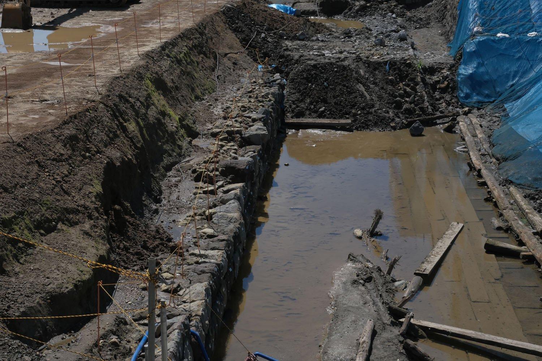上記写真の右側を拡大。開業時の築堤の石垣部分(写真中)、3線化へ増幅時の石垣部分と、水溜りに沈む胴木の板張り(写真右)。
