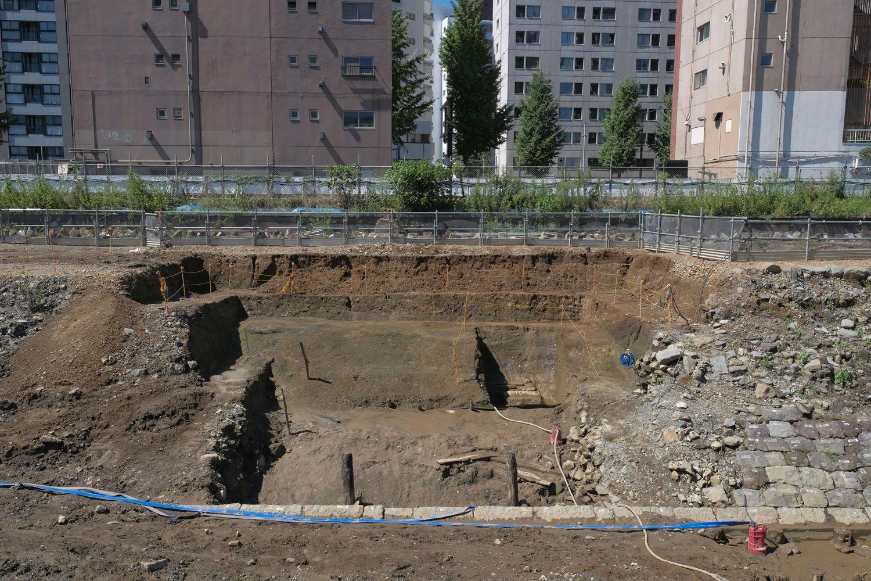 前回紹介した信号機跡より南側の調査箇所。カットされた部分の底辺の粘土質っぽい箇所が築堤の芯となる「築堤基盤」部分となる。右側は石垣が途中から撤去され、雑石と土砂がミックスされた「裏込石」が露出している。