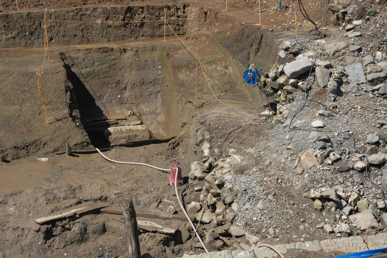 カットした部分を拡大。さらに狭くカットされた部分とその周りがカマボコ状の曲線となっている。その部分が「築堤基盤」となる。右の雑石は裏込石。