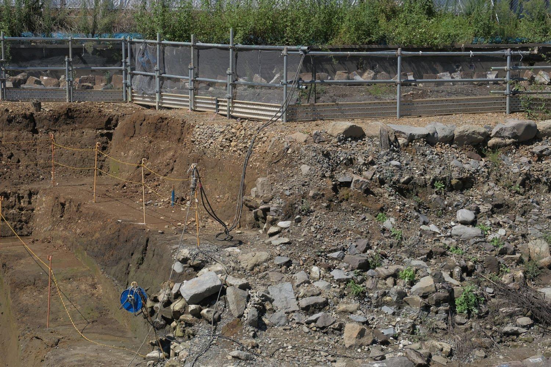柵の下部分の小石は線路敷きに使用されたバラスト。開業時の頃のものらしい。手前でゴツゴツしている石は裏込石だ。